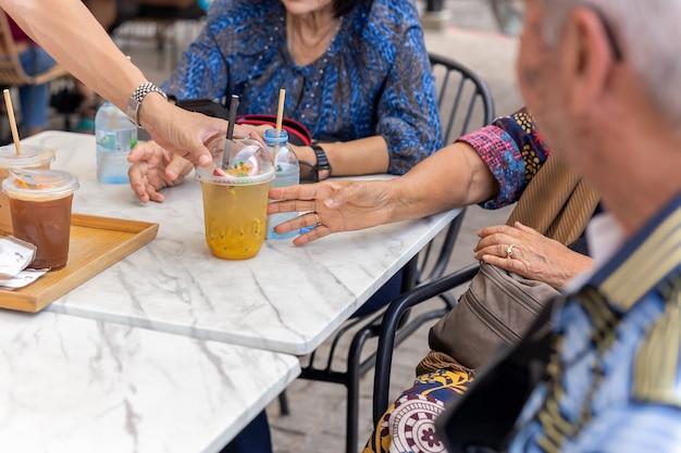 Kellner, der älteren leuten auf dem tisch ein glas frischen saft serviert