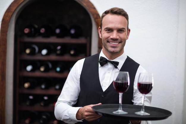 Kellner, der behälter mit rotwein hält