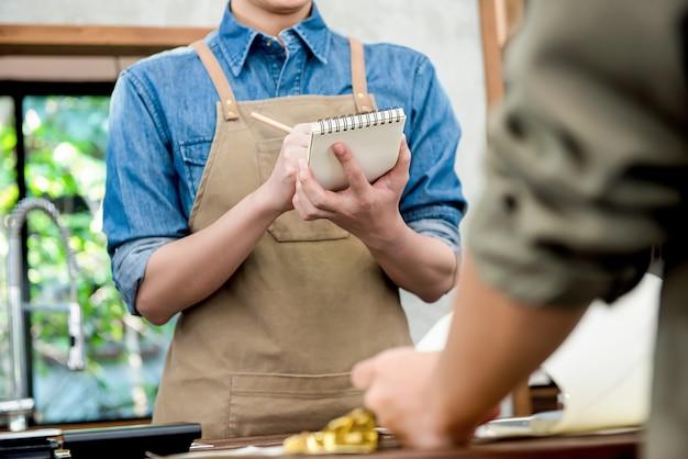 Kellner, der bestellung vom kunden am zähler im café entgegennimmt