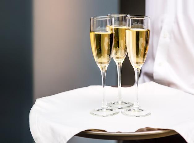 Kellner, der champagnergläser auf einem tablett in einem restaurant serviert.