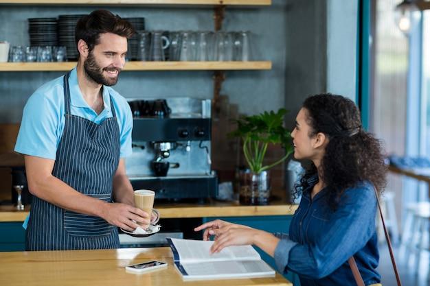 Kellner, der dem kunden am tisch eine tasse kalten kaffee serviert