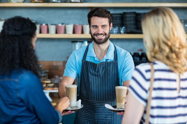 Kellner, der dem kunden an der theke eine tasse kaffee serviert