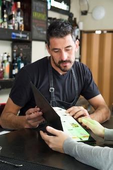 Kellner, der dem weiblichen kunden menü am barzähler zeigt