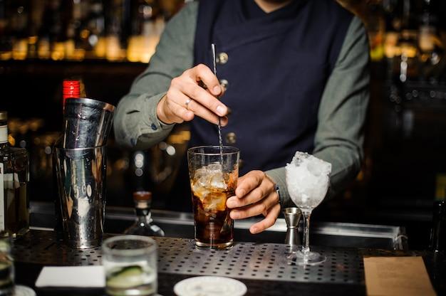 Kellner, der ein alkoholisches cocktail in einem glas macht