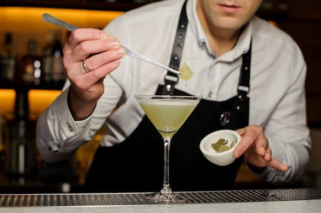 Kellner, der ein birkenblatt verziert ein alkoholisches cocktail setzt