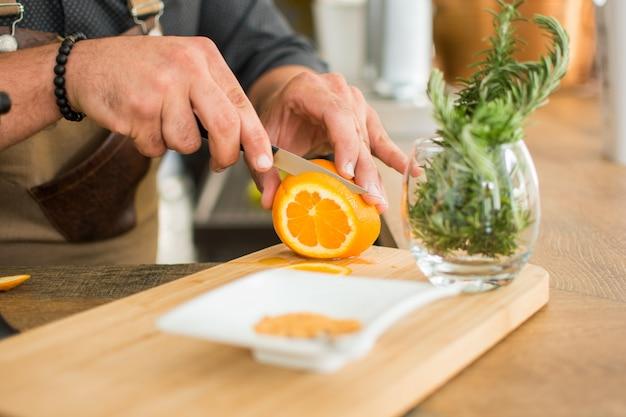Kellner, der ein cocktail schneidet orange vorbereitet