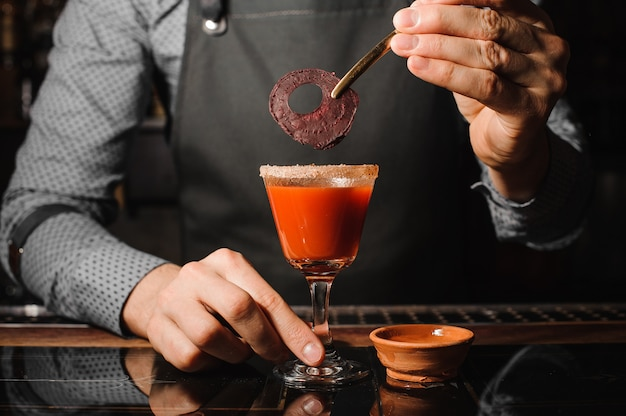 Kellner, der ein cocktailglas füllt mit rotem alkoholischem getränk mit salz und roter rübe verziert