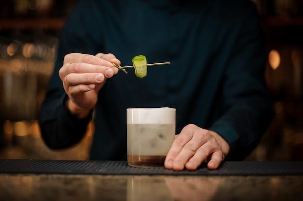Kellner, der ein cocktailglas mit einer gurke auf einer hölzernen aufsteckspindel verziert