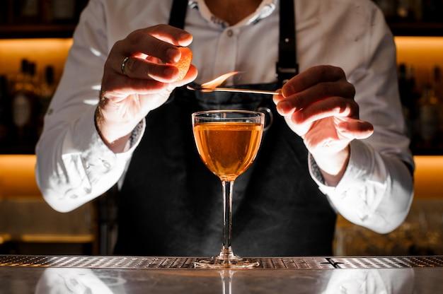 Kellner, der ein frisches alkoholisches cocktail mit rauchiger anmerkung macht