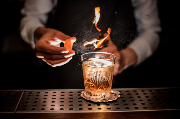 Kellner, der ein frisches und geschmackvolles altmodisches cocktail mit orangenschalen- und rauchanmerkung macht