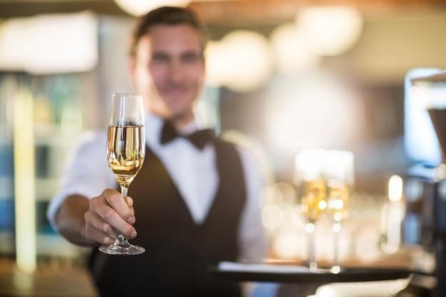 Kellner, der ein glas champagner anbietet