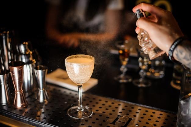 Kellner, der ein glas des alkoholischen cocktails verziert