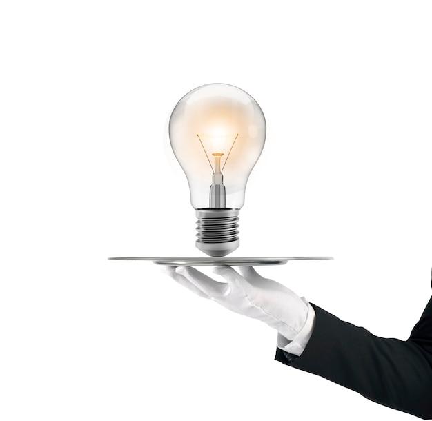 Kellner, der ein tablett mit einer großen idee des glühbirnenkonzepts hält