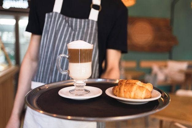 Kellner, der ein tablett mit frischen croissants und kaffee hält.
