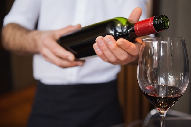 Kellner, der eine flasche rotwein gießt