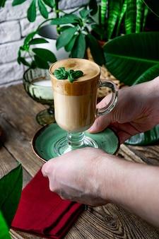 Kellner, der eine tasse lattekaffee in einem kaffeegeschäft, vertikales foto dient.