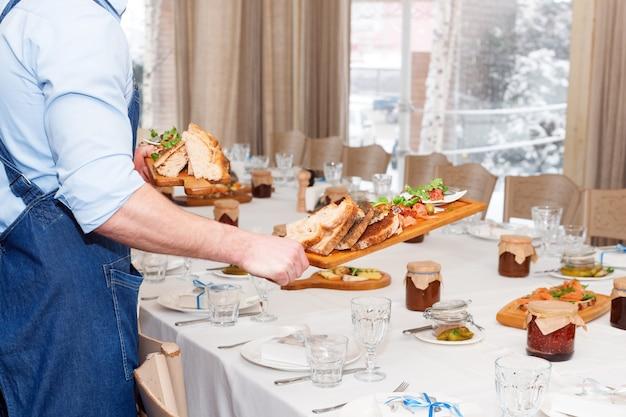Kellner, der fleischgerichte auf holzbrett im restaurant serviert, nahaufnahme.