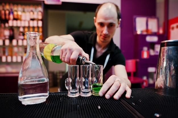 Kellner, der grünes mexikanisches cocktailgetränk an der bar zubereitet