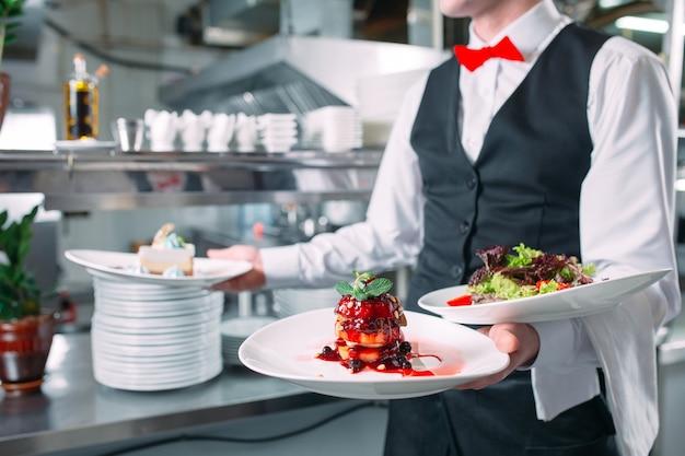 Kellner, der in der bewegung im dienst im restaurant dient. der kellner trägt geschirr.