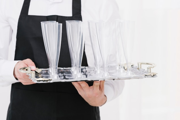 Kellner, der leere gläser auf einem behälter hält