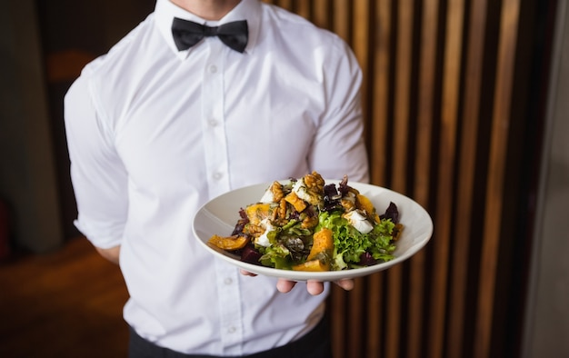 Kellner, der platte des salats zur kamera zeigt