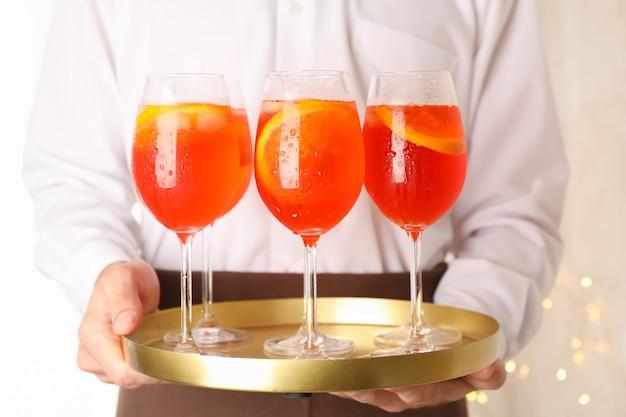 Kellner, der tablett mit aperol-spritz-cocktail hält