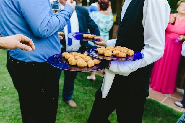 Kellner, die den leuten snacks anbieten, die sie bei einer gesellschaftlichen veranstaltung mit den händen fangen