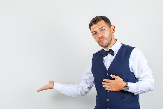 Kellner gestikuliert willkommen in hemd, weste und schaut vorsichtig. vorderansicht.