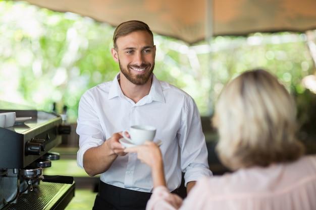 Kellner gibt dem kunden kaffee