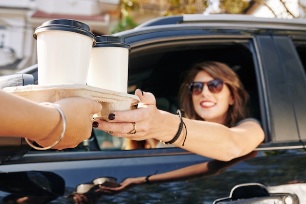 Kellner gibt kaffeetassen an fahrerin
