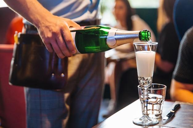 Kellner gießt champagner