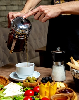 Kellner gießt schwarzen tee aus der französischen presse in den frühstückstisch