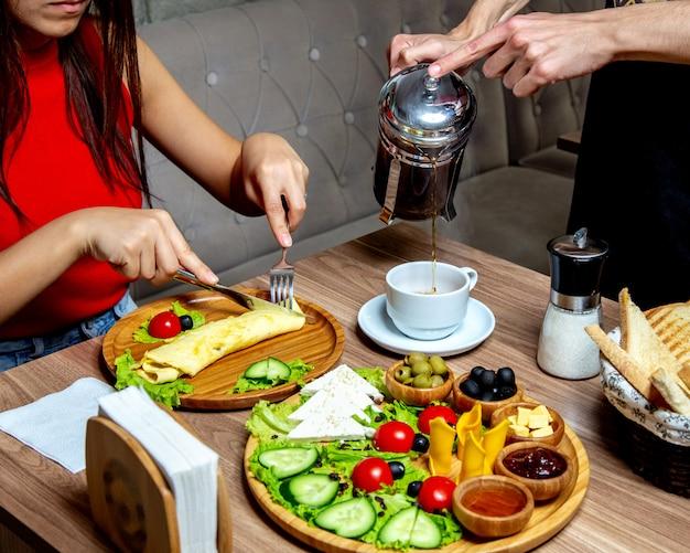 Kellner gießt tee von der französischen presse zu frau, die omelett isst