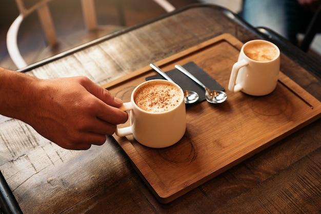 Kellner hält ein tablett mit kaffee in der bar.
