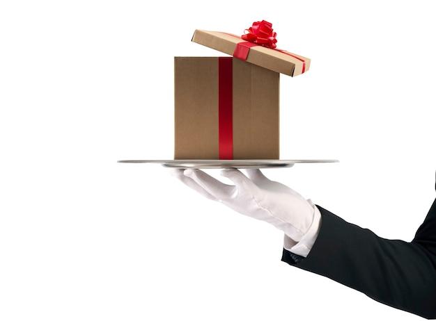 Kellner hält ein weihnachtsgeschenk in einem tablett auf weißer oberfläche isoliert Premium Fotos