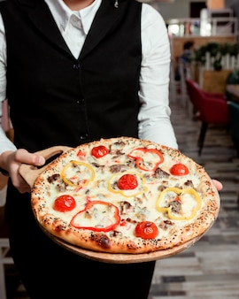 Kellner hält fleischpizza mit gelb-roten paprika-tomaten und käse
