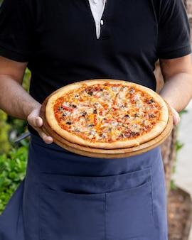 Kellner hält fleischpizza mit roter und gelber paprika
