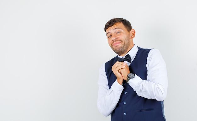 Kellner hält gefaltete hände auf brust in hemd, weste und sieht beschämt aus. vorderansicht.