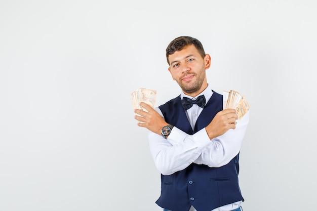Kellner hält geld und lächelt in hemd, weste, vorderansicht.