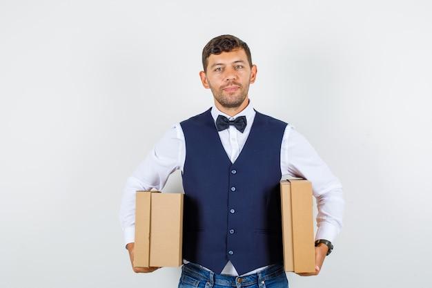 Kellner hält pappkartons und lächelt in hemd, weste, jeans, vorderansicht.