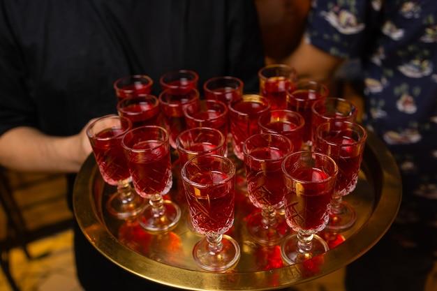 Kellner hält tablett mit aperol spritz cocktail sommergetränk