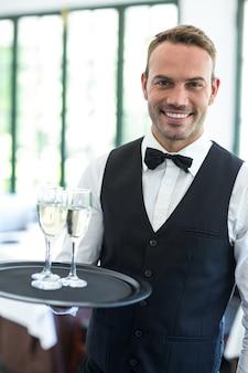 Kellner hält tablett mit champagner