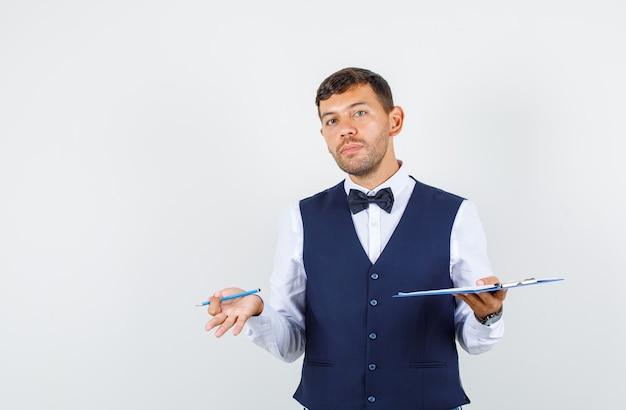Kellner hält zwischenablage und bleistift in hemd, weste und schaut verwirrt, vorderansicht.