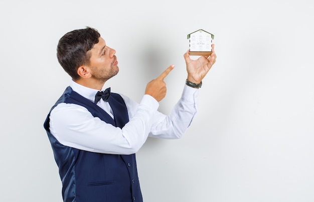 Kellner im hemd, weste zeigt finger auf hausmodell und schaut vorsichtig, vorderansicht.