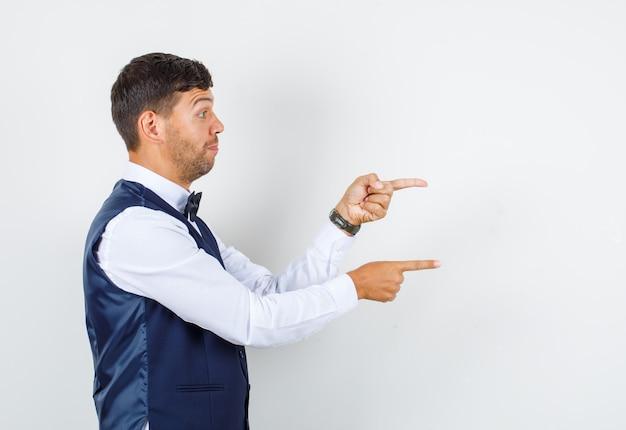 Kellner im hemd, weste zeigt mit den fingern zur seite und sieht motiviert aus.
