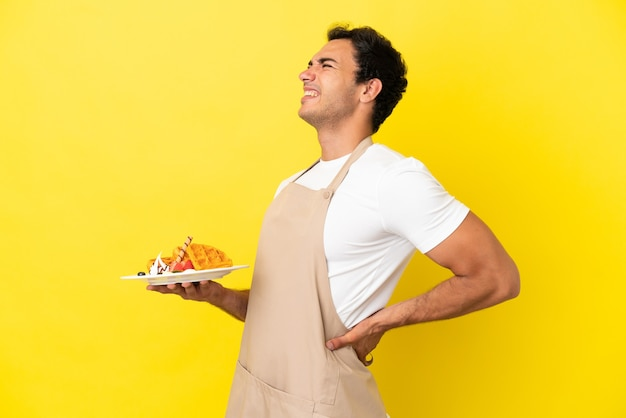 Kellner im restaurant, der waffeln über isoliertem gelbem hintergrund hält, der an rückenschmerzen leidet, weil er sich bemüht hat?