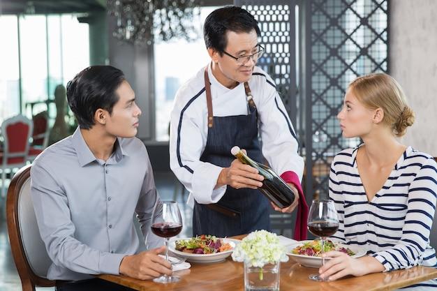 Kellner im restaurant mit wein zu junges paar