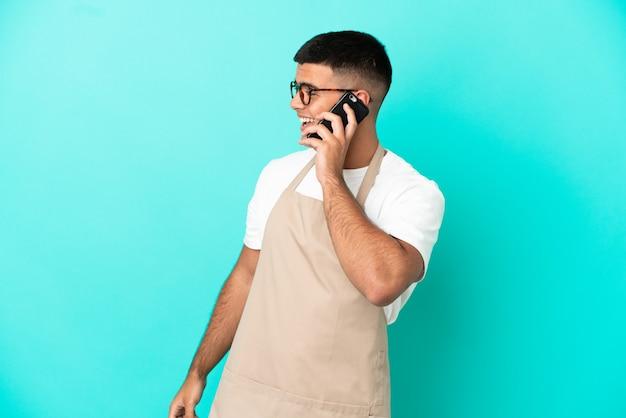 Kellner im restaurant über isoliertem blauem hintergrund, der ein gespräch mit dem mobiltelefon mit jemandem führt