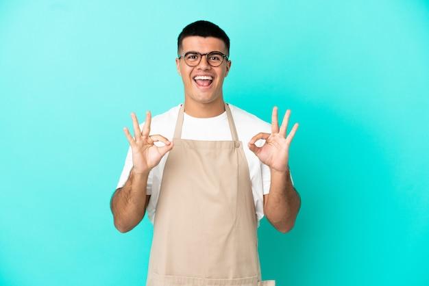 Kellner im restaurant über isoliertem blauem hintergrund, der ein ok-zeichen mit den fingern zeigt