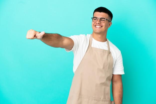 Kellner im restaurant über isoliertem blauem hintergrund, der eine geste mit dem daumen nach oben gibt